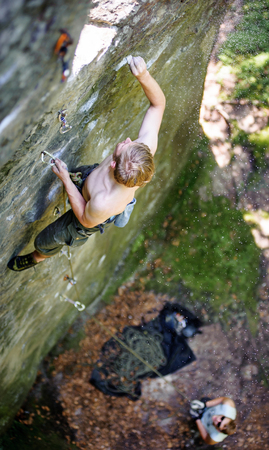 rockclimber: Young man lead climbing on large boulders marking the route, male partner belaying. Outdoor summer day Stock Photo