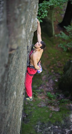 Young man rock-climbing on large boulder. Holding one hand in bag with powder chalk magnesium. Outdoor summer day Stock Photo