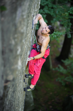 Muscular man rock climber climbs on large boulders with rope engaged. Outdoor summer day Stock Photo