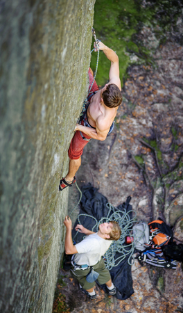 Athletic man lead climber climbing on large boulder securing carbines and rope. male partner belaying. Outdoor summer day