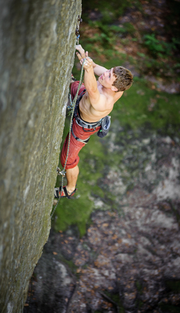Young athletic man rock-climbing on large boulders with rope engaged. Outdoor summer day Stock Photo