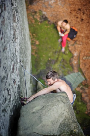 Athletic rock-climber getting over big boulder on steep cliff, his partner belaying