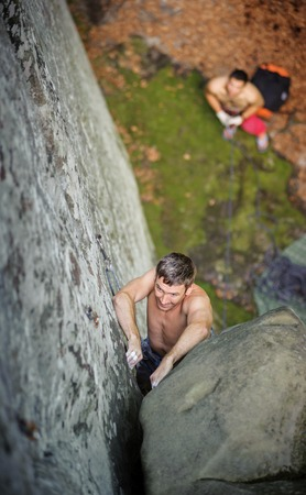 rockclimber: Athletic rockclimber climbing between two large boulders on steep cliff, his partner belaying