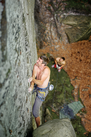 rockclimber: Athletic rock-climber climbing challenging route on cliff rock wall. male pertner belaying