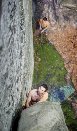 Young rock-climber climbing over big boulder on steep cliff, his partner belaying Stock Photo