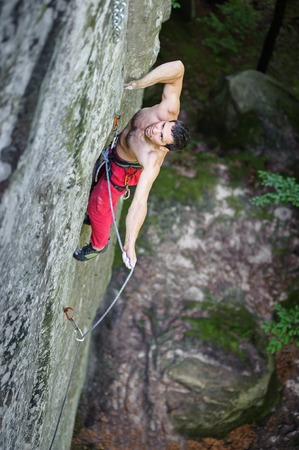 rockclimber: Young athletic man rock-climbing on large boulders with rope engaged. Outdoor summer day Stock Photo