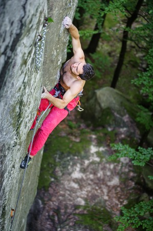 Muscular rock climber climbs on overhanging cliff in summer time Stock Photo