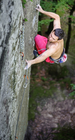 athletic man lead climbing on overhanging cliff securing carabiners and rope. Outdoor summer day