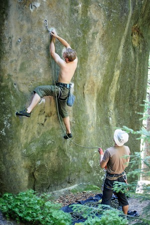 Young man lead climbing on large boulder securing carabiners and rope, male partner belaying. Outdoor summer day Stock Photo