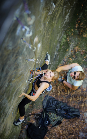 Sporty young woman rock climbing with carbines and rope, man belaying the climber. Looking up