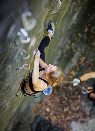 Athletic young woman rock climbing with carbines and rope on summer day. View from the top.