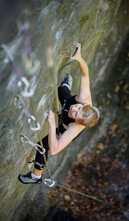 Athletic young pretty girl rock climbing with carbines and rope, bouldering. Smiling and loorking towards the camera. View from the top.