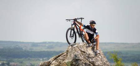 El tipo de la moto en la parte superior de la montaña que se sienta en la roca Foto de archivo - 69777292