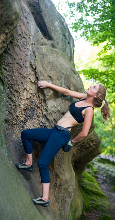 young woman climbing on large boulders outdoor summer day Stock Photo