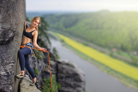conquers: Female extreme climber conquers steep rock over the river
