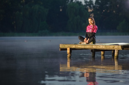 Beautiful young female sitting quietly with her legs crossed in nature on the river, with her eyes closed. Meditation