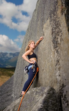 Young beautiful girl climber climbing with rope and carbines on a big rocky wall. Summer time.