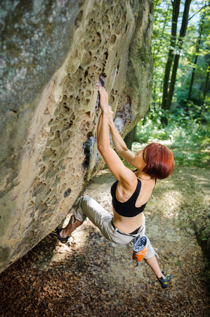 rockclimber: Young athletic woman rock-climber hanging on large boulder. Outdoor Summer day