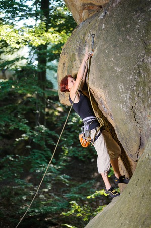 Young female lead climber climbing on large boulder securing carbines and rope. Summer day. Stock Photo
