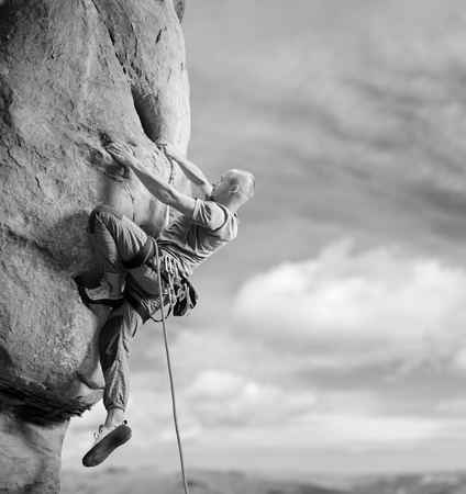 Athletic male lead climber is climbing challenging multi-pitch route with rope on steep rock wall against blue sky. Climbing equipment. Summertime. Copy-space on the right. Black and white Stock Photo