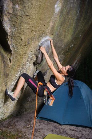 Young woman climber is starting her route on the natural rock wall near camping. Summer time in nature. Climbing equipment. Sport and lifestyle concept.