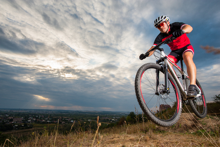 thrill: Mountain biker with helmet jumping against blue evening sky. Low angle portrait. Extrem sport donwhill cyclist