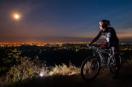 Young cyclist with mountain bike on top of the hill observing the night city view and full moon in the sky
