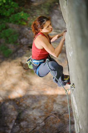 Young beautiful woman climber climbing steep rock with rope, searching for next grip. Top view on focused muscular female athlete. Climbing equipment.