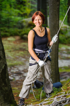 Portrait of beautiful red-haired woman rock climber belaying another climber with rope. Summer time. Climbing equipment.