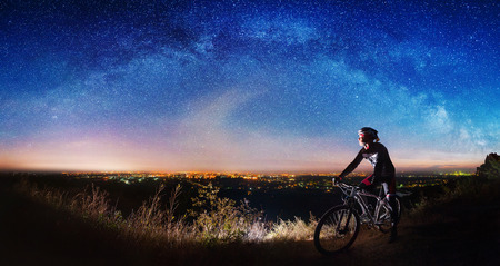 cross country: Cross country biker on top of the hill observing beautiful panoramic view of night sky and city lights.