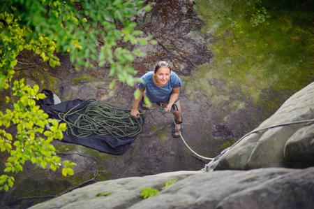 rockclimber: Top view of young athletic woman belaying and watching another climber with rope. Summer time. Climbing equipment. Stock Photo