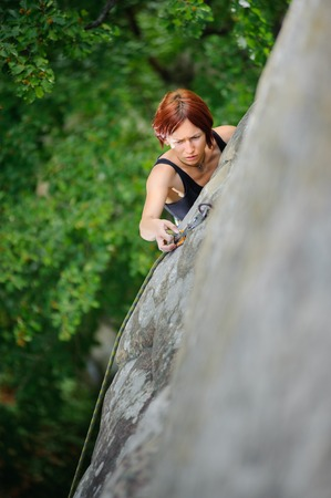 Top view of red-haired athletic woman climbing steep cliff wall in summer time belaying herself. Sport and Healthy lifestyle concept.