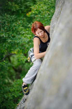 Top view of red-haired athletic woman climbing steep cliff wall in summer time. Sport and Healthy lifestyle concept. Climbing equipment