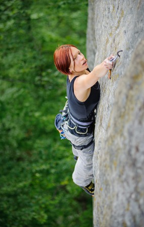 Beautiful strong female climbing steep stone wall in nature. Woman lead climber fastening carabiner at the next grip. Top view.