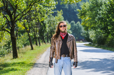 Portrait of a young biker man with beard standing on the road. Biker is wearing leather jacket and blue jeans.