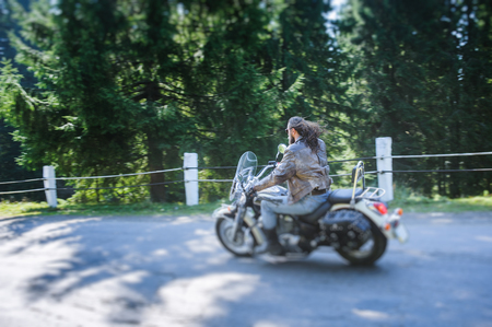 Man with beard driving his cruiser motorcycle by nice road in the forest. Man is wearing leather jacket and blue jeans. Back view. Tilt shift lens blur effect