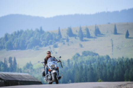 Biker in sunglasses on mountainous road, man is riding his custom made travel motorbike. Sunny day in the mountains. Tilt shift soft effect