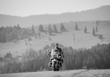 Handsome biker in sunglasses on mountainous road, man is riding his custom made travel motorbike. Sunny day in the mountains. Tilt shift soft effect. Black and white