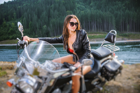 Portrait of young sexy lady with long hair wearing leather jacket and short shorts sitting on custom made cruiser motorcycle by the river with forest on the background. Tilt shift lens blur effect