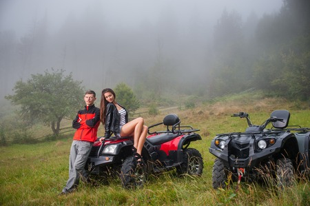 Happy couple near four-wheeler ATV in foggy nature. Smiling and looking at the camera Stock Photo