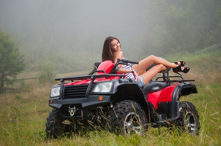 Beautiful girl sitting on four-wheeler ATV. Wearing high heels smiling and looking towards the camera