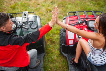Couple sitting on four-wheeler ATV giving high five. View from the back Stock Photo