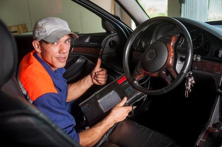 Diagnosi del meccanico auto lo sterzo nel servizio di riparazione auto. Guardando verso la telecamera e alzando il pollice