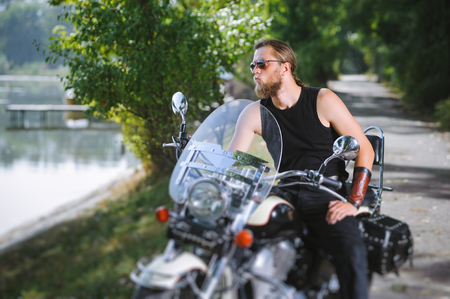 joyride: Handsome biker in sunglasses with long hair and beard sitting on his motorcycle near the lake on a sunny day. Tilt shift lens blur effect. Stock Photo