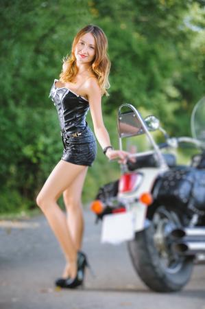 sexualidad: Atractiva mujer joven que llevaba ropa de cuero sexy y tacones altos. Hembra hermosa que presenta cerca de la motocicleta del crucero. Caluroso día de verano al aire libre. cambio de inclinación efecto de desenfoque de lente Foto de archivo