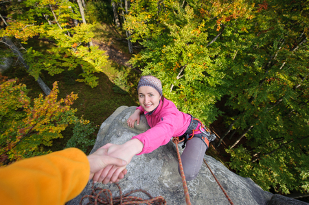 A male rockclimber is helping a young beautiful female climber to reach a peak of mountain. Man giving a hand to the woman.
