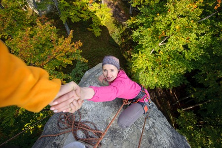 rockclimber: Rockclimber is helping a young beautiful girl to climb to the peak of mountain. Man giving a hand to the woman. Warm autumn evening