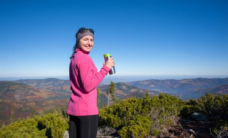 Young lady hiker smiling holding the flask and looking at the camera. Happy woman enjoying beautiful day up on the mountain. Colorful fall time.