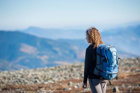 Young woman enjoying nature on backpacking trip in the mountains. Girl is looking into distance, rear view. Stock Photo