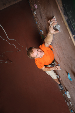 Young man climbing on practical wall in gym, bouldering. reaching the top, smiling and looking at the camera